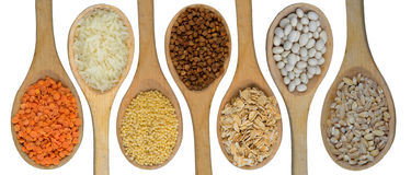 Wooden spoons full of grains Royalty Free Stock Image