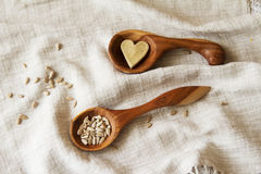 Wooden spoons hand on the table. Composition of wooden spoons on a drapery spilling seeds. Spoons from apricot wood Stock Photography
