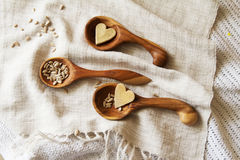 Wooden spoons hand on the table. Composition of wooden spoons on a drapery spilling seeds. Spoons from apricot wood Royalty Free Stock Photo