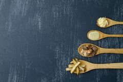 Wooden spoons with ingredients to prepare meat with potatoes and cilantro royalty free stock photography