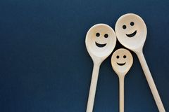 Wooden spoons look like happy family. Smiling faces.  Stock Photography