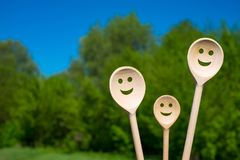 Wooden spoons look like happy family. Smiling faces.  royalty free stock photography