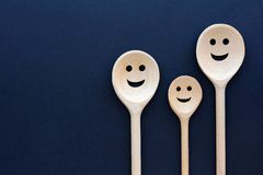 Wooden spoons look like happy family. Smiling faces.  Stock Photos