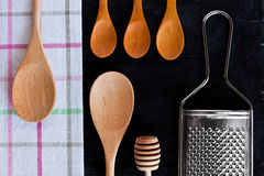 Wooden spoons, metal grater and tablecloth Stock Photography