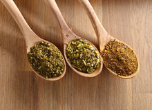 Wooden spoons with mixture of different  spices on kitchen table Royalty Free Stock Image