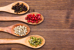 Wooden spoons with peppers mixed one hand on wood Royalty Free Stock Photo