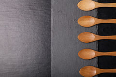 Wooden spoons on a plate of slate on a black background Stock Images