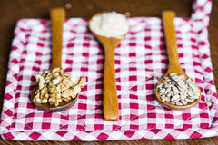 Wooden spoons with raw nuts on checkered red dishtowel Stock Images