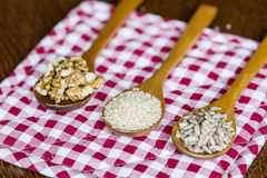 Wooden spoons with raw nuts on checkered red dishtowel Royalty Free Stock Photo