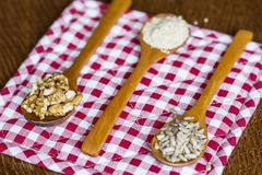 Wooden spoons with raw nuts on checkered red dishtowel Royalty Free Stock Image