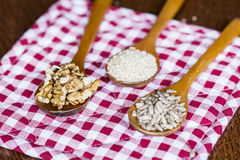 Wooden spoons with raw nuts on checkered red dishtowel Royalty Free Stock Photos