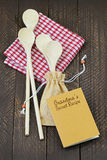 Wooden spoons on red gingham tablecloth and a small notebook. Top view of wooden spoons in beige fabric sack on red gingham tablecloth and a small notebook Stock Image
