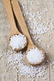 Wooden spoons with sea salt closeup on wooden rustic table. Background stock photos