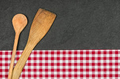 Wooden spoons on a slate plate. With a red checkered tablecloth Stock Photography