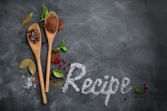 Wooden spoons with spices and recipe word Stock Photos