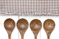 Wooden spoons and tablecloth on the white table Royalty Free Stock Images