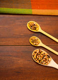 Wooden spoons with toasted corn grains, known as tostado in south america, spread around bowl containing yellow salsa Royalty Free Stock Images