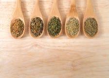 Italian herbs on wooden spoons royalty free stock photos