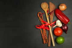 Wooden spoons and vegetables on a black table. Food preparation. Royalty Free Stock Photography