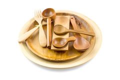 Wooden spoons in wooden plates isolated on white background Stock Photos