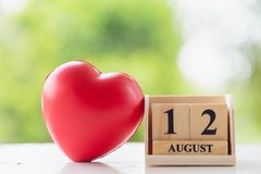 Wooden square block number 12 August with a red heart shape ball on wooden floor royalty free stock image