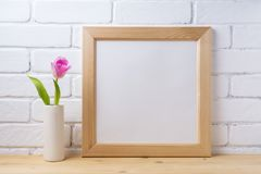 Wooden square frame mockup with pink tulip. Wooden square picture frame mockup with pink tulip in cylinder vase near painted brick wall. Empty frame mock up for royalty free stock image