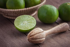 Wooden squeezer and lime on table Royalty Free Stock Photos