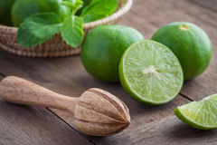 Wooden squeezer and lime on table Royalty Free Stock Images