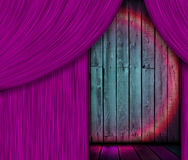 Wooden Stage Behind Purple Curtain. A wooden stage with a spotlight behind a purple curtain Royalty Free Stock Photography