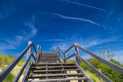 Wooden staircase and blue sky among dunes and high grass Stock Image