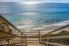 Wooden Stairs Lead Down onto Malibu California Beach. Wooden staircase descends down onto beach with vast ocean all the way to horizon.  Taken at El Matador Stock Images