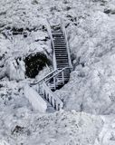 Wooden staircase frozen in ice, covered with icicles against a frozen lava field covered with ice and snow stock photography