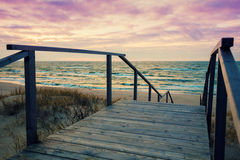 Wooden staircase with a handrail. To the sea at sunset stock photo