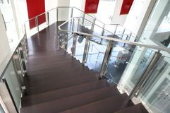 A wooden staircase leading down with walls of glass. An interior photo taken on a flight of wooden staircase leading down in a lobby with walls of glass Stock Images