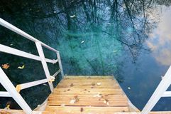 Wooden staircase leading to clear blue water outdoors. Wooden staircase leading to clear blue water outdoors Stock Photography