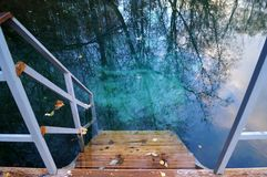 Wooden staircase leading to clear blue water outdoors. Wooden staircase leading to clear blue water outdoors stock photo