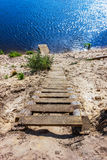 A wooden staircase leads down to the river. A homemade ladder on the steep slope of the river Royalty Free Stock Photos