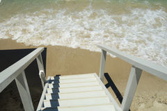Wooden staircase to a Mediterranean beach. Wooden stairs walkway leading to a sandy beach on a summer day stock photos