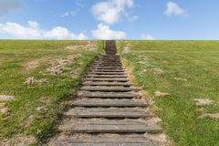Wooden stairs upon green hill with blue sky Royalty Free Stock Photos