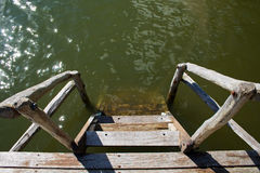 Wooden stairs lead into water. Royalty Free Stock Photography