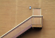Wooden Stairs Leading to a Door in the middle of a Wall Stock Photography