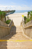 Wooden stairs leading to the ocean. Stairs leading to a beautiful beach showing the pier and ocean in the background Stock Images