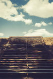 Wooden stairs leading up to the blue sky with white clouds Stock Images