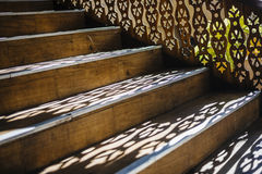 Wooden stairs with light-shadow play. Royalty Free Stock Photography