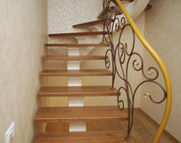 Wooden stairs and metal tracery forged railing. Royalty Free Stock Images