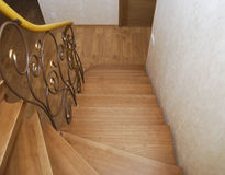 Wooden stairs and metal tracery forged railing. Royalty Free Stock Photos
