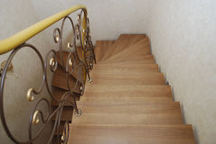 Wooden stairs and metal tracery forged railing. Royalty Free Stock Image