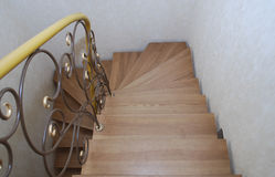 Wooden stairs and metal tracery forged railing. Royalty Free Stock Photography