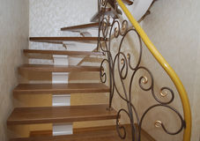 Wooden stairs and metal tracery forged railing. Royalty Free Stock Photo