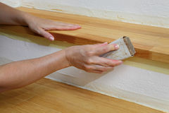 Wooden stairs sanding, home renovation. Worker sanding plank at stairs using sand paper Royalty Free Stock Photo